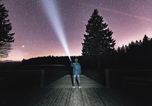 Leuchtender Strahl der Taschenlampe in den Sternen Himmel