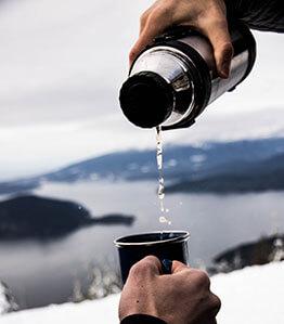 Aus Thermoskanne ein warmes Getränk in einen Becher füllen