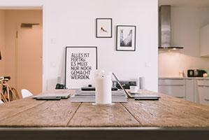 Arbeitstisch mit Laptop und Kerzen, im Hintergrund hängen Bilderrahmen