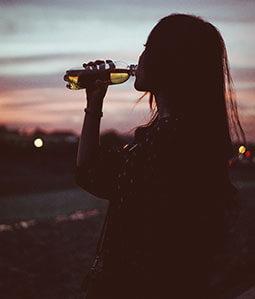 Eine Frau trinkt aus einer Trinkflasche in der Abenddämmerung