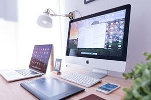 Schreibtisch mit PC, Laptop und Handy