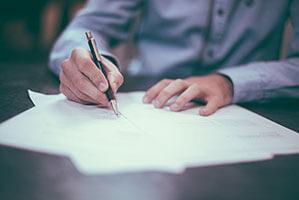 Auf einem Papier mit einem Kugelschreiber unterschreiben