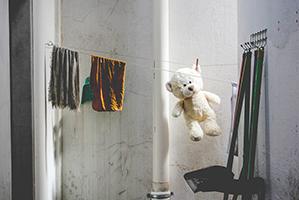 Einen grauen und einen oker farbenen Waschlappen hängen mit einem weißen Teddybären an einer Wäscheleine