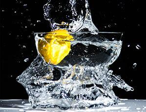 Sprudelndes Glas Wasser mit einer Zitronenscheibe