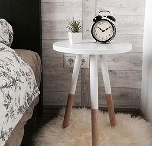 Kleiner Vintage Wecker auf Nachttisch neben dem Bett