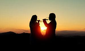 Pärchen trink Wein im Sonnenuntergang
