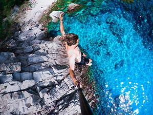 Klippenspringer, Mann springt von hohem Fels in türkis/blaues Wasser mit einer Action-Cam in der rechten Hand