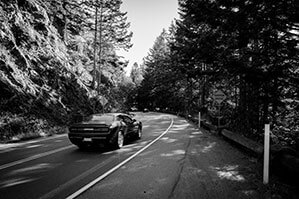 Auto auf einer Straße im Wald neben Bergen