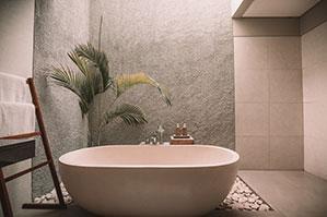 Ovale Badewanne mit Palme und Handtuchablage