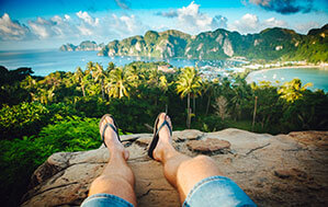 Mann mit Flip Flops auf Fels, im Hintergrund Meer und Palmen