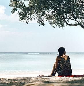 Frau sitzt am Strand unter Baum und schaut auf das Meer