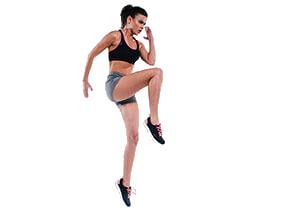 Eine Frau im Fitness Outfit, springt hoch mit einem Bein