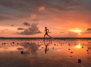 Am Strand joggen im Sonnenuntergang