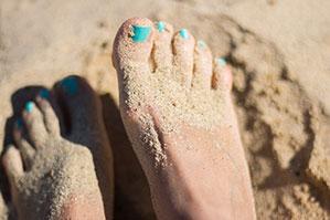 Füße mit Türkisem Nagellack im Sand