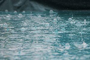 Regentropfen auf Wasser