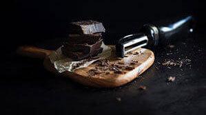 Dunkle Schokolade auf Brettchen mit Raspel