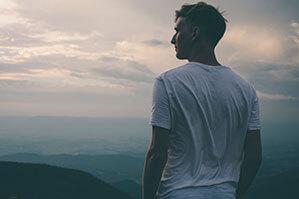 Mann mit weißem T-Shirt in Berge