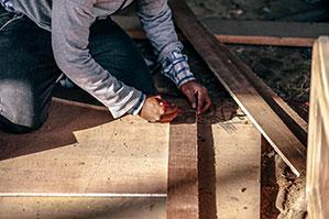 Heimwerker kniet auf dem Boden und zeichnet auf Holz