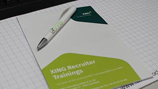 Der Werbe-.Block mit Logo für XING wurde mit einem SChutzumschlag versehen, auf dem Sie wieder den Werbkugelschreiber Boogie sehen.