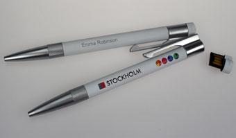 Sie sehen zwei weiß lackierte Metall-Kugelschreiber mit integrioertem USB-Stick Stockholm, sowohl bedruckt, als auch graviert wurden.