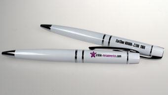 Sie sehen zweio weiß lackierte Metall-Kugelschreiber VIP von UMA, die mit dem mesoamerika-Logo und deren Telefonnummer bedruckt wurden.