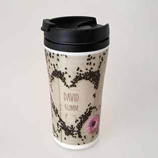 Ein weißer Thermobecher mit schwarzem Deckel, der rundum mit einem Motiv aus Kaffeebohnen auf Holz bedruckt ist. In einem Herz aus Kaffeebohnen steht als Einzelnamen-Veredelung ein Name geschrieben.