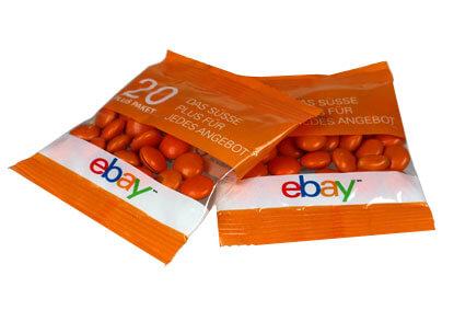 Zwei Werbetütchen mit Logodruck von ebay. Die Tütchen sind größtenteilsorange gehalten und haben ein Sichtfenster, durch das man die orangenen Schokolinsen s´gut sehen kann.