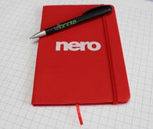 """Ein rotes Notizbuch mit Verschlussband und Lesezeichen, auf dessen Deckel n Weiß das nero-Logo gedruckt wurde. Über dem Logo liegt ein Schwarzer Kugelschreiber """"Boogie"""" mit laprinta-Logo."""