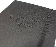 Ein schwarzes Notizbuch, das mit einer Holz-Maserung geprägt ist, in welches das Logo des Hotel Kempinsky geprägt wurde