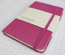 Ein rosanes Notizbuch von Moleskine®, auf dessen Deckel ein Slogan geprägt wurde.