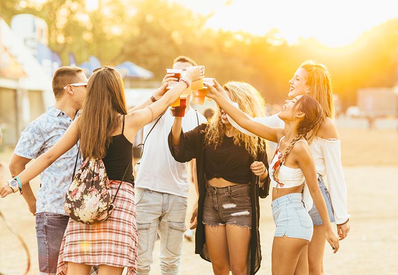 Eine Gruppe junger Leute steht im kreis und streckt die Getränke in die Luft