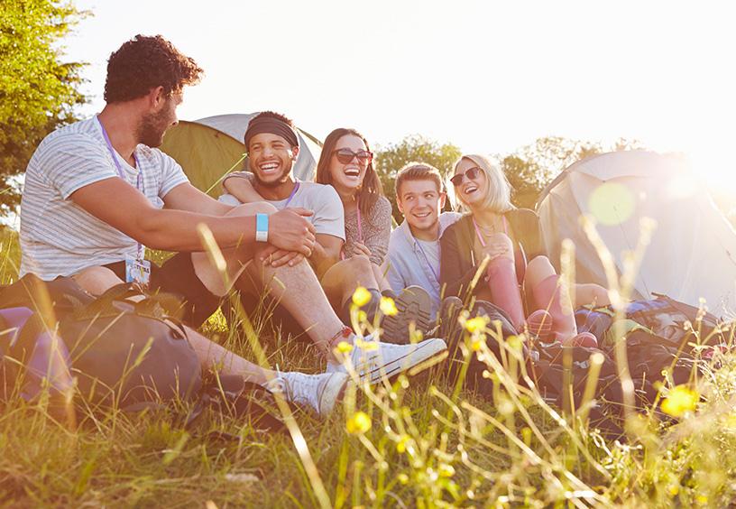 Eine Gruppe aus Männern und Frauen sitzen in der Wiese und lachen, im Hintergrund ist ein kleines Zelt