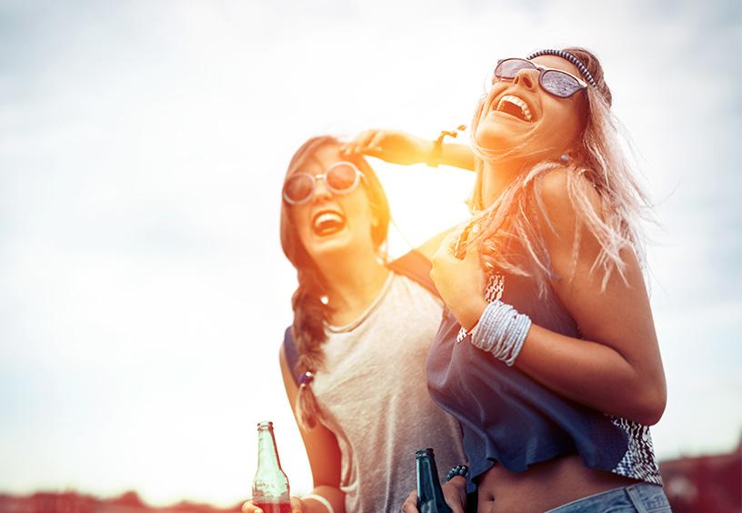 Zwei Frauen mit Sonnebrille haben Spaß, lachen und sind glücklich im Sonnenuntergang