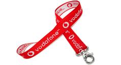 Rotes Schlüsselband, liegend, mit eingewebtem Vodafone-Logo und Schriftzug. Innen invertierter Logo-Stick