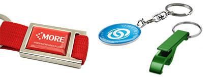 Ein roter Schlüsselanhänger mit einem Logo-Doming, ein SChlüsselanhänger in Wunschform und ein grüner Flaschenöffner-Anhänger