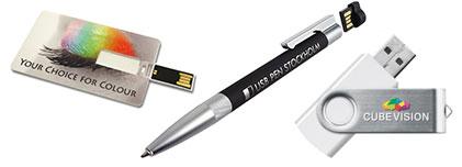 Eine USB-Karte im Scheckkartenformat (aufgeklappt), ein gravierter USB-Kugelschreiber mit dem Speicherchip im Drücker und ein USB-Stick Twister mit Logodruck