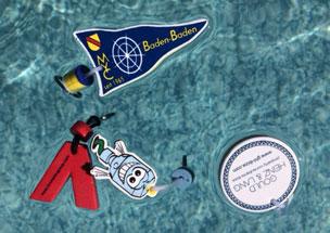 Verschiedene schwimmfähige Schlüsselanhänger in Wunschform mit Kunden-Werbedruck, die in einem Pool schwimmen